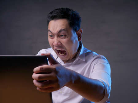 Young Asian man wearing casual white shirt looking at laptop, angry gesture. Bad news or failure in business concept