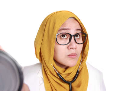 Female Asian muslim doctor holding a stethoscope, seriously listening gesture, doctor checking with stethoscope