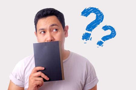 Jonge Aziatische man met een boek met denkende expressie. Close-up portret tegen een witte achtergrond Stockfoto