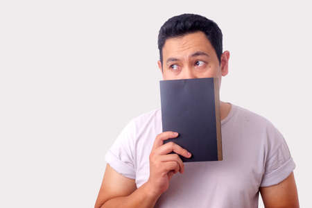 Young Asian man holding a book with thinking expression. Close up portrait against white background