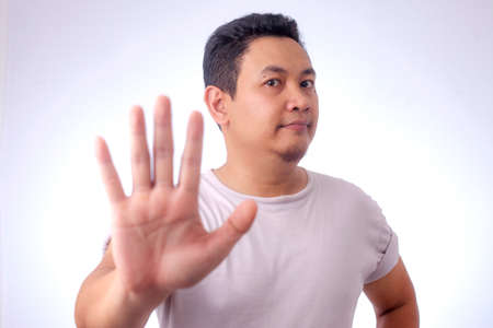 Portrait of young Asian man shows stop gesture with his finger over grey background Stockfoto