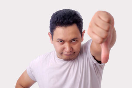 Photo image portrait of a funny young Asian man doing mocking gesture with synical face and showing two thumbs down over white background