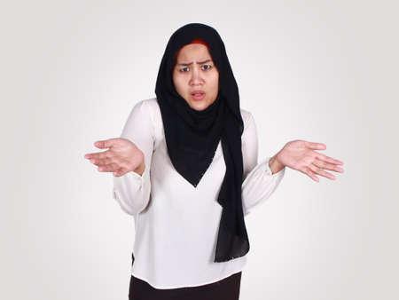 Porträt einer asiatischen muslimischen Frau, die mit den Schultern zuckt, Verleugnung oder ich weiß nicht, Geste isoliert auf weiß