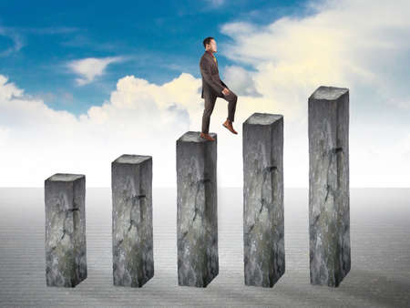 Businessman walking up on business growth diagram made of stone, success chart graphic concept Stock Photo