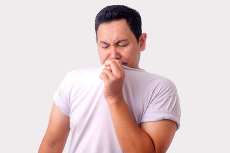 Portrait of funny young Asian man smelling his own body, bad body odor problem Stock Photo