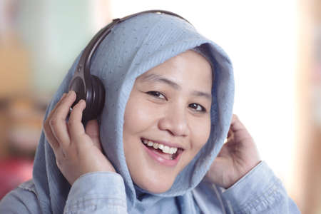 Portrait of young beautiful Asian muslim woman wearing hijab listening music with a headphones Stock Photo