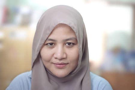 Portrait de belle femme musulmane portant le hijab souriant sur fond flou