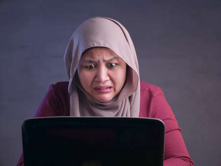 Portrait of muslim businesswoman wearing hijab shocked stunned when looking at laptop, bad negative news concept Stockfoto