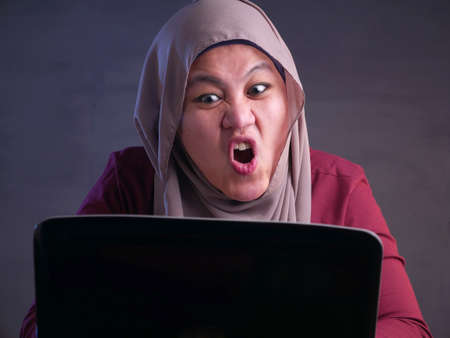 Portrait of Asian muslim businesswoman working on laptop at the office, mad angry upset expression Stockfoto