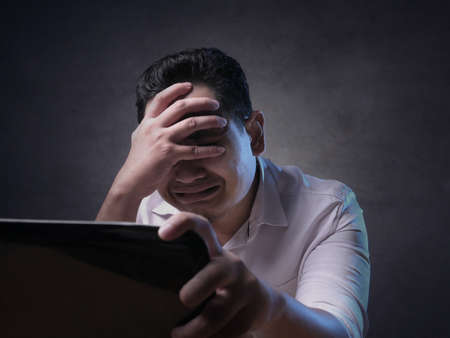 Portrait of young Asian man looked crying upset disappointed stress and headache to see bad things on internet, bad business concept