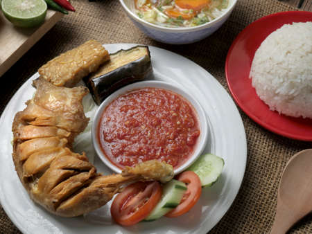 Food photography, Indonesian fried chicken or ayam goreng served with sambal and white rice Stockfoto