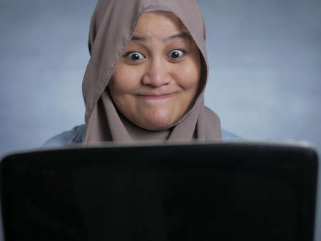 Portrait of muslim woman wearing hijab using laptop with shocked stunned excited facial expression gesture, having good news on internet concept