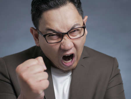 Angry Asian businessman showing his fist, ready to fight while screaming, anger madness in business concept
