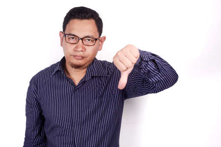 Photo image portrait of a funny young Asian man doing disappointed gesture with synical face and showing thumb down over white background