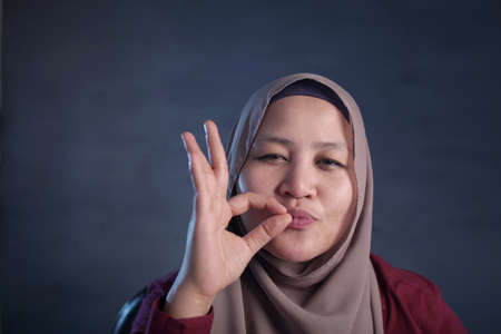 Portrait of beautiful Asian muslim woman smiling while making delicious hand gesture with her fingers