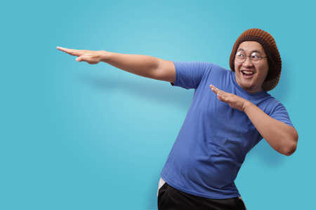 Portrait of funny Asian man smiling and making dab movement, against blue background Reklamní fotografie