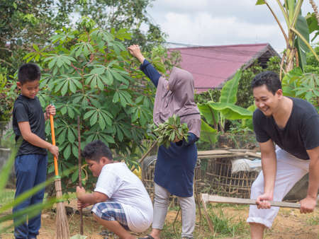 Portrait of happy healthy Asian family gardening at their backyard