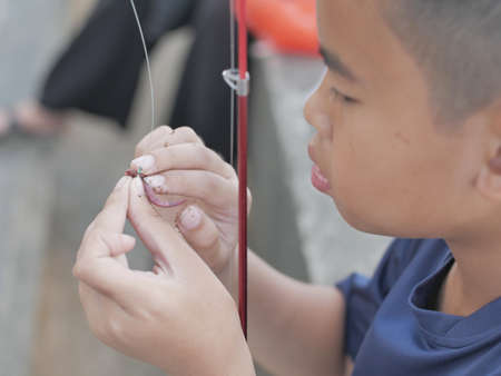 Close up image of young Asian boy put a worm on a hook, worm fishing day 写真素材
