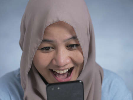 Portrait of young Asian muslim woman get good news on her phone, happy surprised expression Stockfoto - 130470091