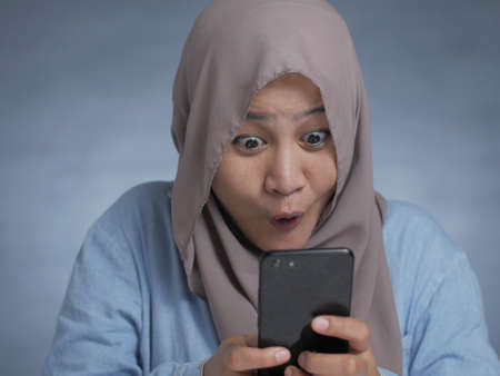 Portrait of young Asian muslim woman get good news on her phone, happy surprised expression Stockfoto - 130470093