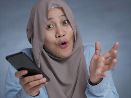 Portrait of young Asian muslim woman get good news on her phone, happy surprised expression Stockfoto - 130470090