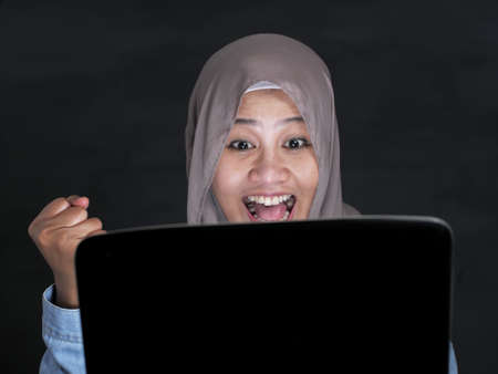 Portrait of Asian muslim lady using laptop, shows happy surprised expression celebrating winning victory gesture after receiving good news on her email