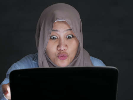 Portrait of muslim woman wearing hijab using laptop with shocked stunned excited facial expression gesture, having good news on internet concept Stockfoto - 130470140
