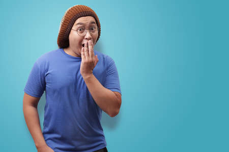 Portrait of young funny Asian man shocked or surprised expression, stunned excited gesture while covering his mouth with hand, against blue background