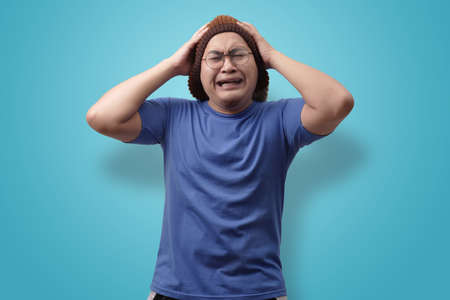 Portrait of funny Asian man crying close his eyes, sad depression frustration hopeless expression, against blue background Stock Photo