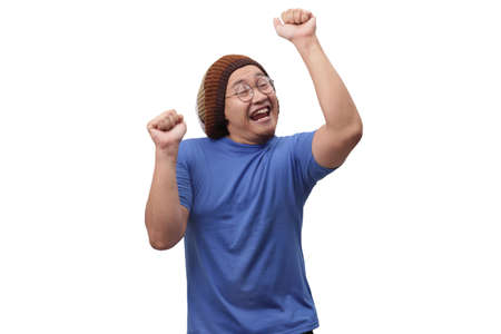 Portrait of a funny young Asian man wearing blue shirt dancing happily joyful expressing celebrating good news victory winning success gesture, smiling positive excited emotion isolated on white Stockfoto