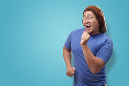 Portrait of a funny young Asian man wearing blue shirt dancing happily joyful expressing celebrating good news victory winning success gesture, smiling positive excited emotion Stockfoto