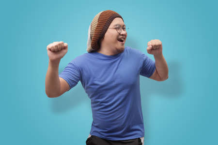 Portrait of a funny young Asian man wearing blue shirt dancing happily joyful expressing celebrating good news victory winning success gesture, smiling positive excited emotion Stockfoto - 130470784