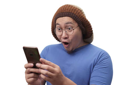 Portrait of happy funny Asian man shocked or surprised with mouth open, good news on smart phone concept, amazed winning gesture Stockfoto - 130470988