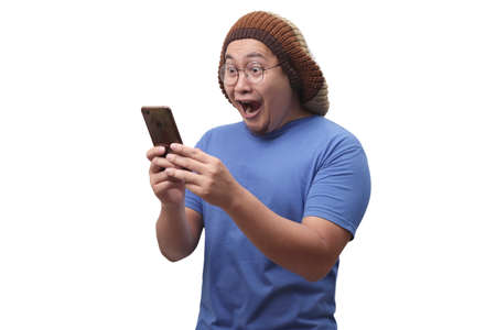 Portrait of happy funny Asian man shocked or surprised with mouth open, good news on smart phone concept, amazed winning gesture Stockfoto - 130470987