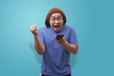 Portrait of happy funny Asian man shocked or surprised with mouth open, good news on smart phone concept, amazed winning gesture