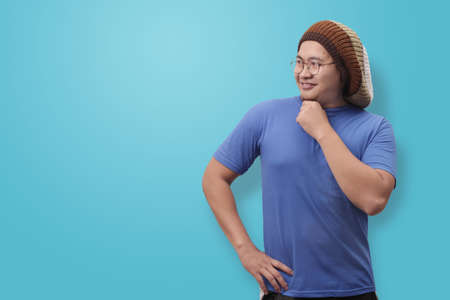 Photo image portrait of funny young attractive cute Asian man smiling happily, with arms on hip looking to the side Banque d'images