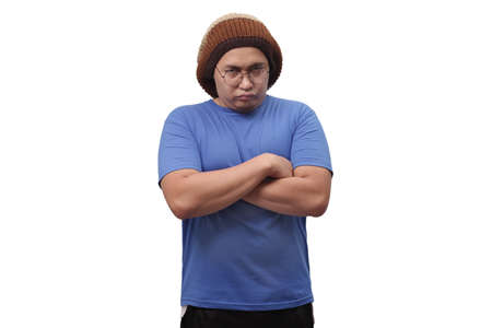 Portrait of young Asian man standing with arms crossed and shows upset cynically annoyed gesture, isolated on white Stock Photo
