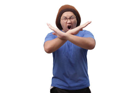 Portrait of young funy angry Asian man shows crossed arms gesture, giving warn to stop gesture, rejection concept 스톡 콘텐츠