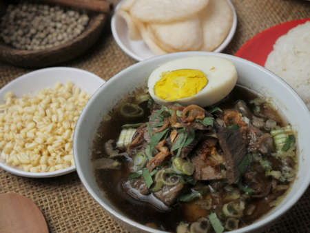 Food photography, rawon or Indonesian black beef soup, served with rice, hard boiled egg, bean sprouts and crackers Banco de Imagens