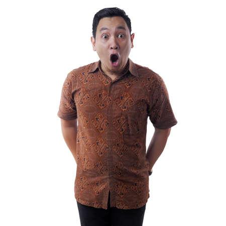 Retrato de joven asiático en camisa batik, gesto de sorpresa con la boca abierta. Aislado en blanco Foto de archivo