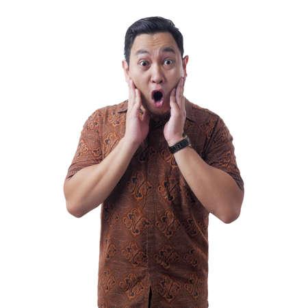 Retrato de joven asiático en camisa batik, gesto de sorpresa con la boca abierta. Aislado en blanco