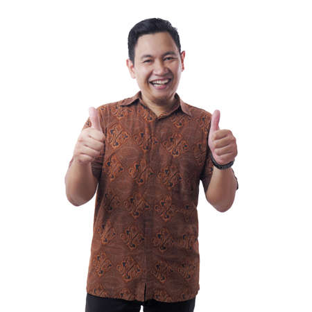 Portrait of attractive young Asian man wearing batik shirt smiling and showing thumbs up sign, isolated on white 免版税图像