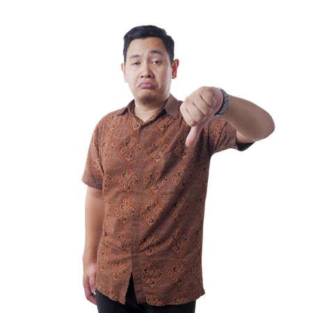 Porträt eines attraktiven jungen asiatischen Mannes, der Batikhemd trägt, der eine spöttische Geste mit synischem Gesicht macht und Daumenzeichen zeigt, isoliert auf weiß
