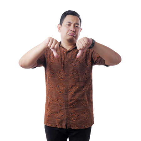 Portrait of a attractive young Asian man wearing batik shirt doing mocking gesture with synical face and showing thumbs sign, isolated on white