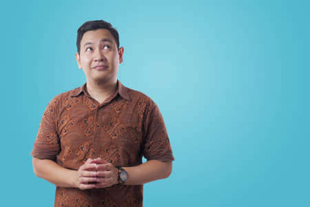 Portrait of young Asian man wearing batik shirt looked happy thinking and looking up, having good idea. Half body portrait against blue background