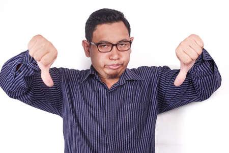 Fotoporträt eines lustigen jungen asiatischen Mannes, der eine spöttische Geste mit synischem Gesicht macht und zwei Daumen nach unten über weißem Hintergrund zeigt Standard-Bild