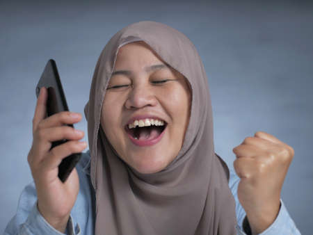 Portrait of young Asian muslim woman get good news on her phone, happy surprised expression Stockfoto - 130477130