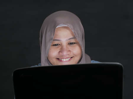 Portrait of Asian muslim woman working on laptop, smiling happy expression, good news on email or excitement of watching movies on streaming media concept Stockfoto - 130477137