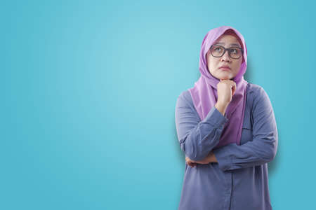Asian muslim woman wearing hijab with thinking expression. Looking for solution of a problem. Close up portrait against blue background 版權商用圖片