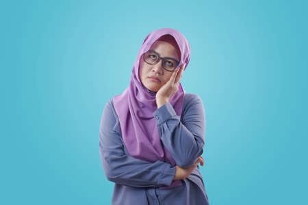 Portrait of young Asian muslim woman showing tired diizzy sluggish gesture, against blue background